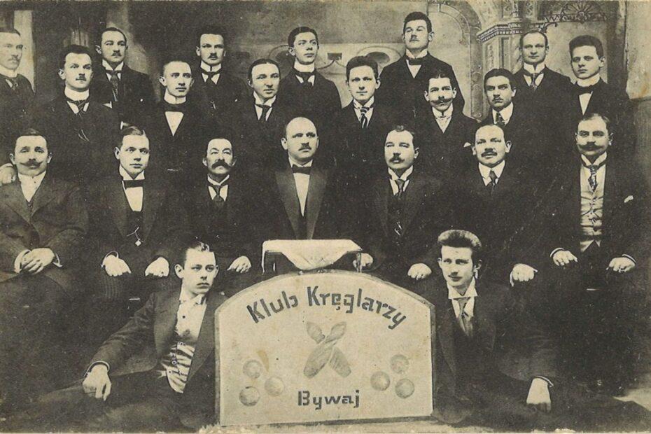 Fotografia przedstawiająca grupę mężczyzn. Przed nimi tablica z napisem klub kręglarzy bywaj.